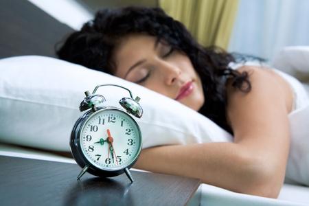 Image of alarm clock on background of sleeping female photo