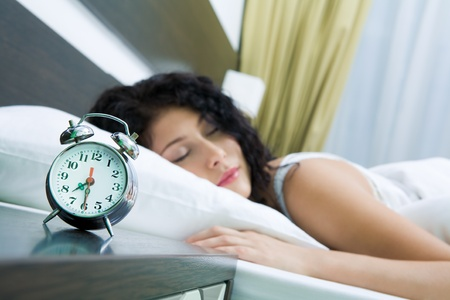 Image of alarm clock on background of sleeping female photo