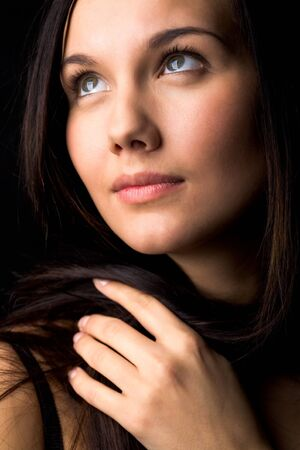 chins: Image of young female with dark hair touching it by hand