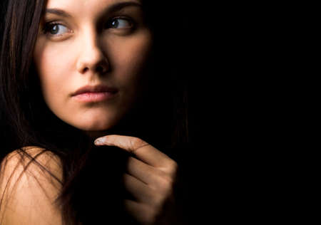 aside: Image of gorgeous lady with dark hair touching it by hand and looking aside