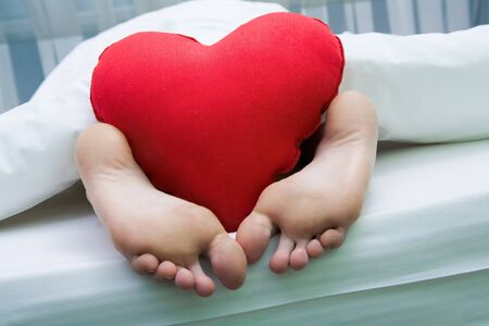 nice body: Image of bare feet with red soft heartshaped pillow