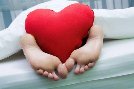 partes del cuerpo humano: Imagen de pies descalzos con almohada rojo heartshaped suave