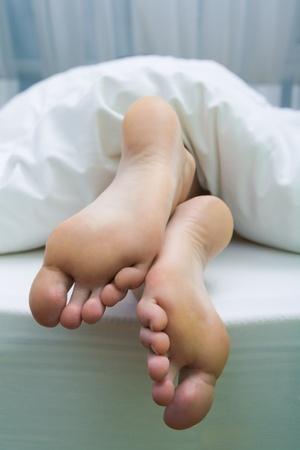 white linen: Imagen de pies descalzos apuntando de manta de lino blanco