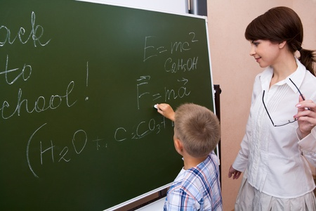 additional chemicals: Photo of elementary student writing formulae on blackboard with his teacher near by