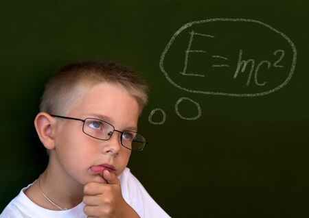 lad: Photo of pensive lad by the blackboard touching his chin while thinking of difficult formula