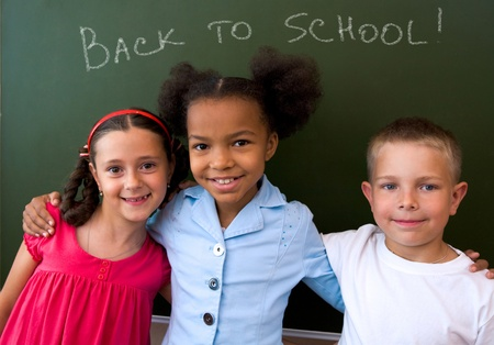 Image of clever schoolchildren standing by blackboard and looking at camera  Stock Photo - 8448271