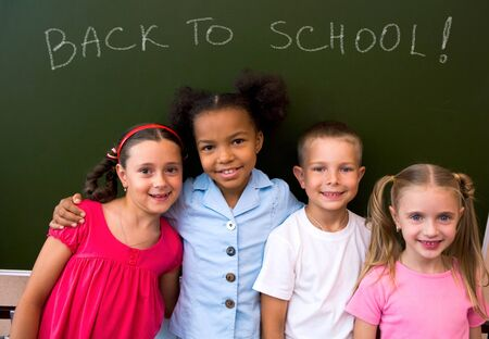 Image of clever schoolchildren standing by blackboard and looking at camera Stock Photo - 8448233