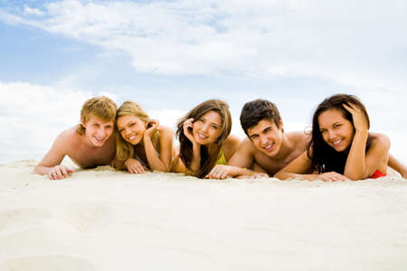Row of cheerful friends lying on sandy beach and smiling at camera photo