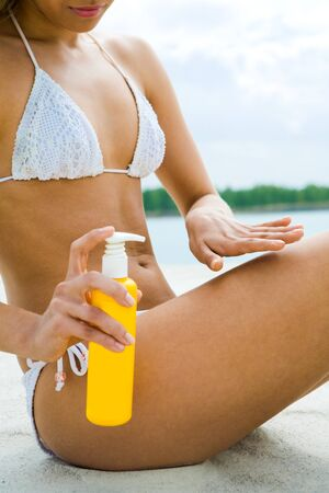 Image of female in white bikini holding suncare lotion while spreading it on leg Stock Photo - 8448333