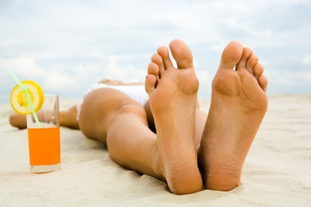 weekends: Close-up of two human feet on sandy beach with cocktail near by