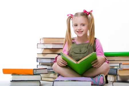 schoolchild: Image of happy pretty girl sitting and holding book