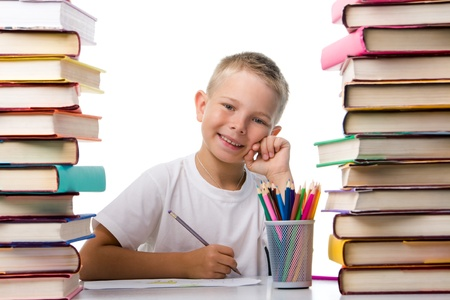 Portrait of cute youngster sitting among stacks of literature and smiling at camera while drawing photo