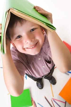 diligente: Ojo de pez disparo de chico diligente con libro sobre su cabeza mientras que hacer deberes Foto de archivo