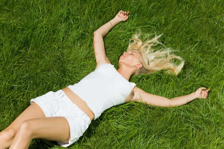 Above view of serene girl lying on green grass with stretched arms photo