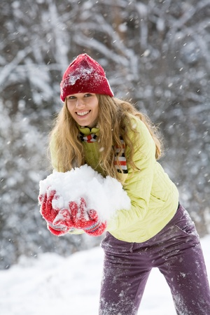 Portrait of beautiful woman holding snow and smiling