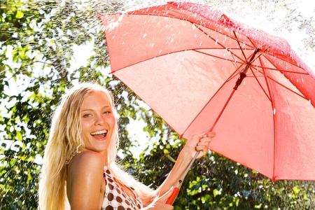 Portrait of happy girl with red umbrella looking at camera in park photo