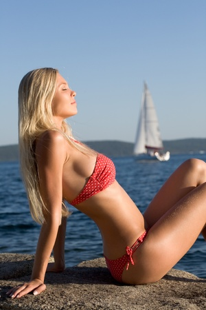 Photo of beautiful blonde sitting by the sea and sunbathing photo