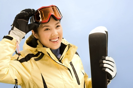 Portrait of sport woman holding her skis and touching glasses photo