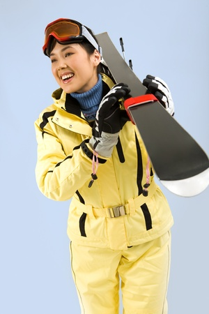 Portrait of pretty woman in sportswear carrying her skis  photo