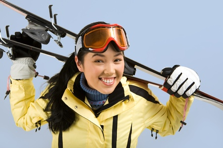 Portrait of smiling girl with sport glasses holding the skis on her back  photo