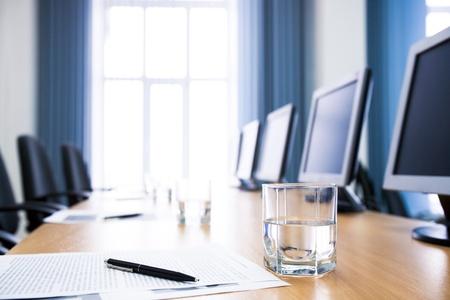 Obraz szklankę wody na miejscu pracy z papieru, pióro i monitory niedaleko przez