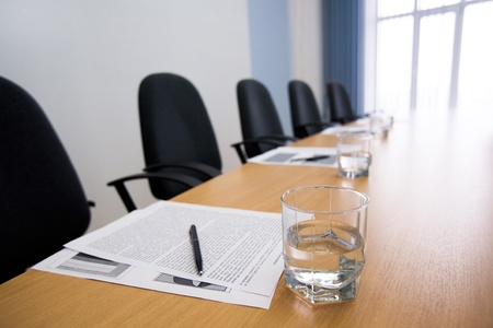 meeting place: Image of glass of water on workplace with paper, pen and armchairs near by Stock Photo