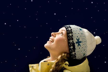 Portrait of amazed girl looking at falling snowflakes photo