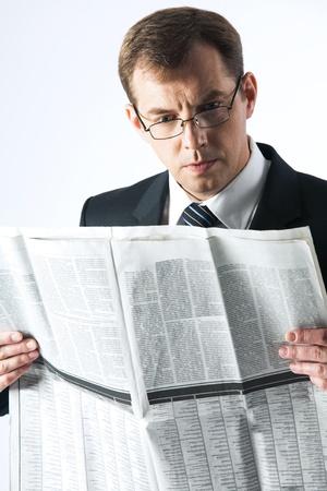 amused: Vertical image of amused businessman reading newspaper