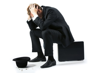 Portrait of sad businessman sitting on the floor with hat and coins near by Stock Photo - 8454971