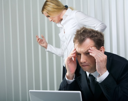 Photo of stressed businessman touching his head with secretary at background photo