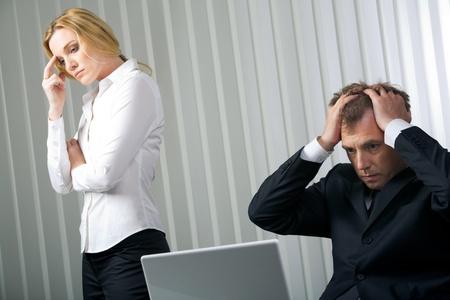 gente triste: Foto del empresario acentuado tocar su cabeza con una mujer triste cerca por
