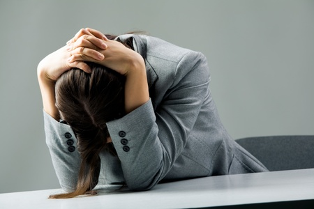 white collar worker: Photo of depressed female sitting at workplace and grieving Stock Photo