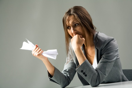 Photo of depressed female with neglected hair looking at paper in her hand and grieving photo