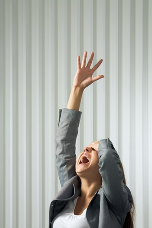 Photo of unhappy female shouting with her arm raised in pray Stock Photo - 8455113