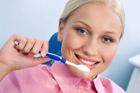 Image of happy female with toothbrush looking at camera and smiling Stock Photo - 8455149