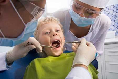 Dental inspection is being given to little boy surrounded by dentist and his assistant Stock Photo - 8455189