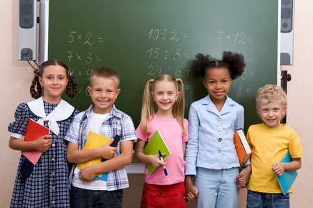 Image of curious schoolchildren standing by blackboard and looking at camera in the classroom photo