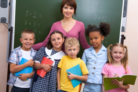 schoolchild: Line of cute schoolchildren looking at camera with their teacher near by Stock Photo