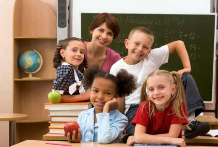 Group of smart schoolkids and their teacher looking at camera in classroom Stock Photo - 8455219
