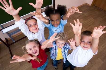 schoolchildren: Image of cute schoolchildren looking at camera and laughing with their arms raised Stock Photo