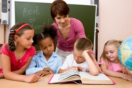 Image of group of schoolchildren and teacher reading book together in the classroom