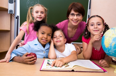 classroom teacher: Portrait of teacher and children looking at camera in the classroom