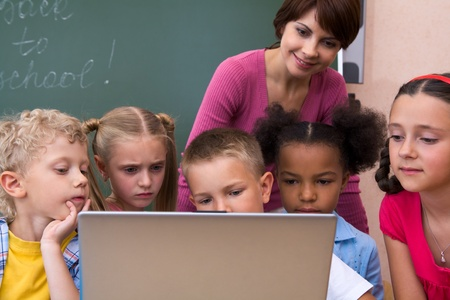 Portrait of pupils looking the laptop with teacher near by  photo