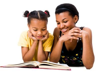 ni�os leyendo: Imagen de la mujer y la ni�a leyendo el libro juntos Foto de archivo