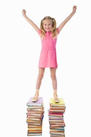 diligent: Diligent preschooler standing on the top of book stairs with her arms raised