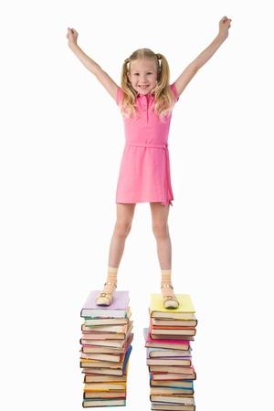 diligente: Ni�o en edad preescolar diligente de pie en lo alto de las escaleras de libro con sus brazos alzados Foto de archivo