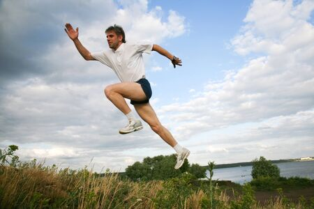Horizontal image of active man jumping near lake Stock Photo - 8455377