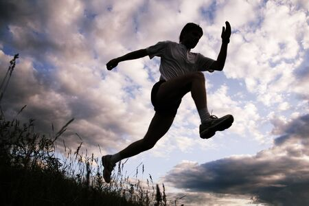 jogging in nature: Photo of silhouette of jumping sportsman on a sky background