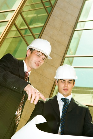 Portrait of two confident workers discussing a project near building  photo