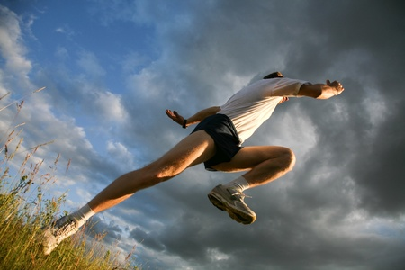 View from below: athlete raising leg and hand Stock Photo - 8455391